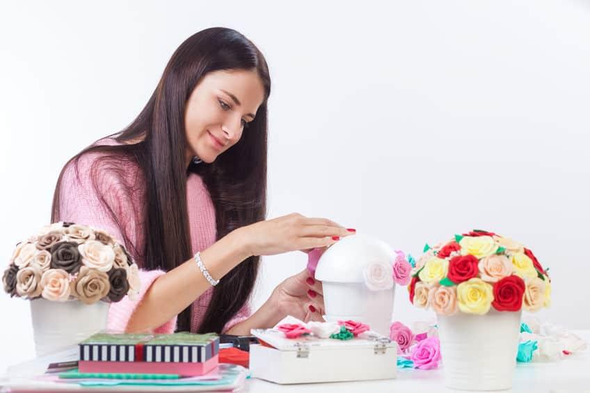 Mulher customizando um vaso de flores artificiais.