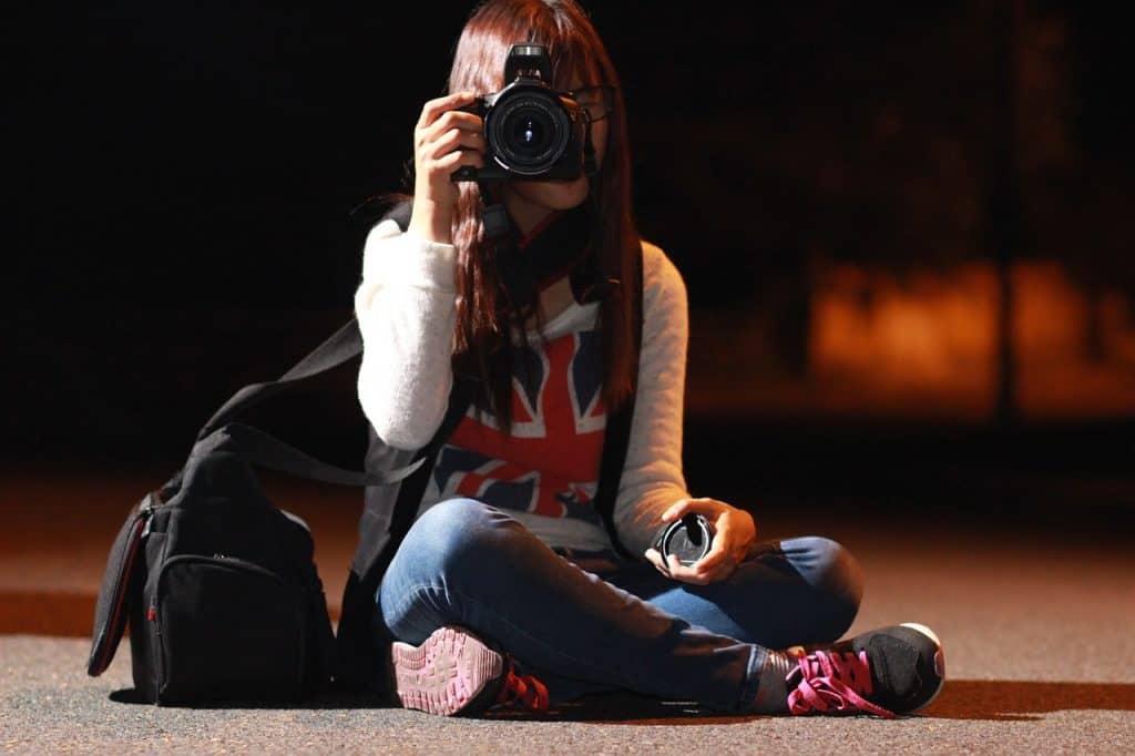 Imagem mostra uma pessoa sentada no chão tirando fotos com uma câmera DSLR.