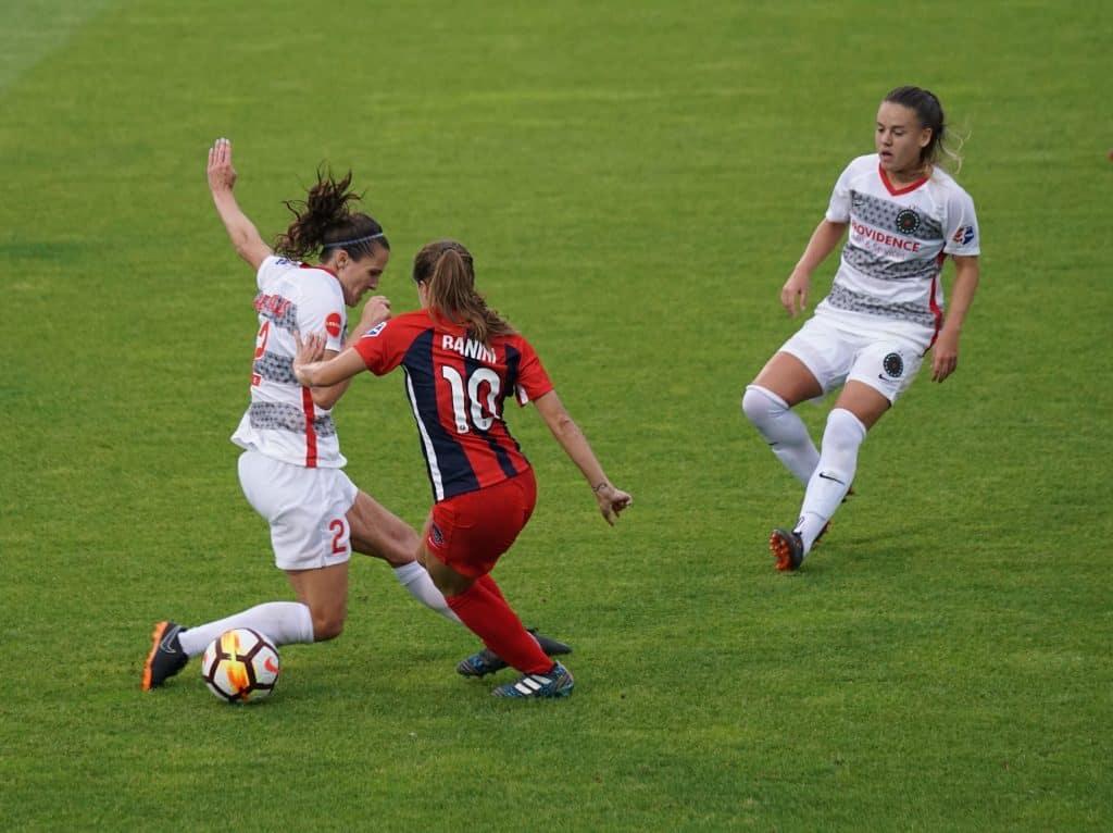 Imagem mostra duas jogadoras adversárias disputando a bola durante um jogo, observadas por uma terceira jogadora, à direita.