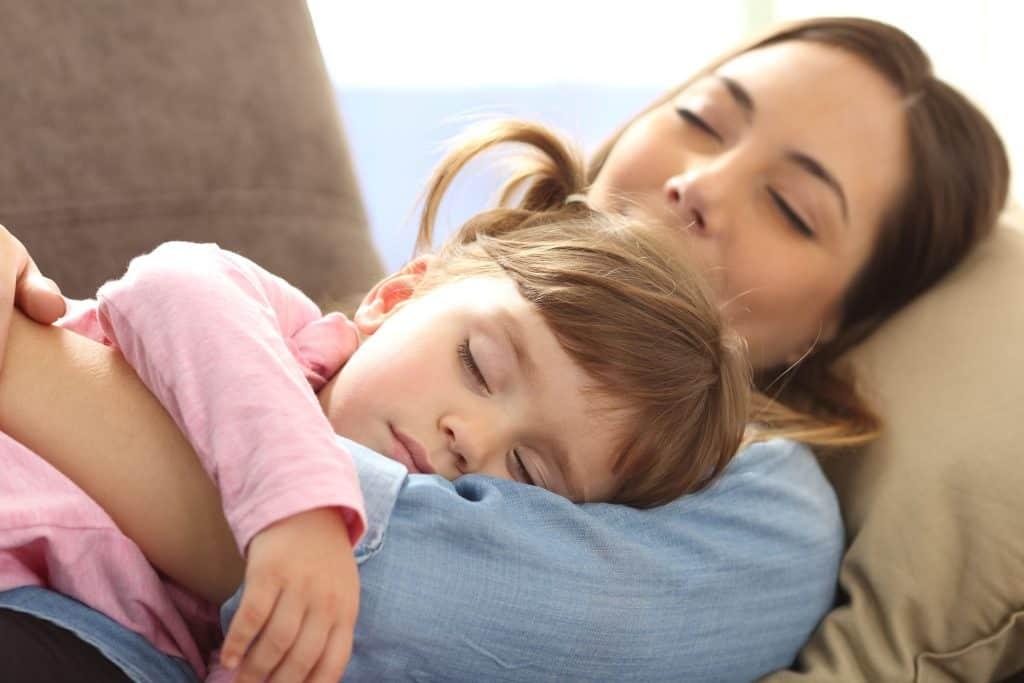 Imagem de mãe e filha dormindo.