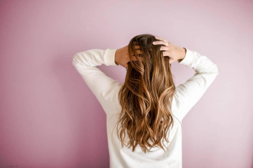 Foto de uma mulher de cabelos castanhos claros, de costas, virada para uma parede rosa, com as mãos na cabeça.