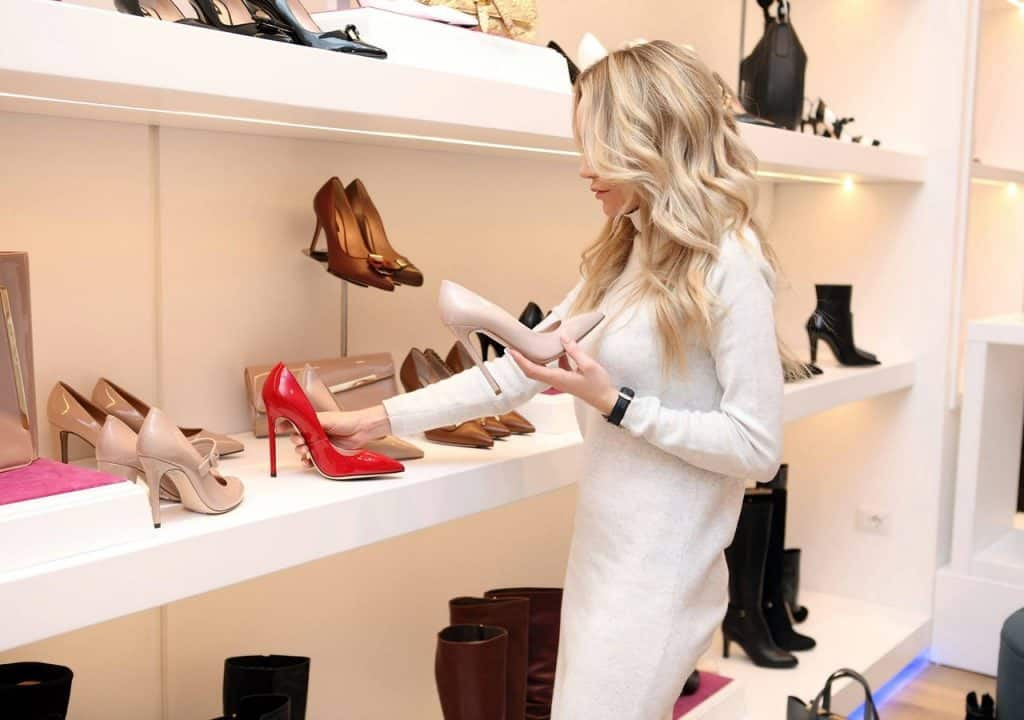 Foto de uma mulher loira de vestido branco, organizando sapatos em um closet.