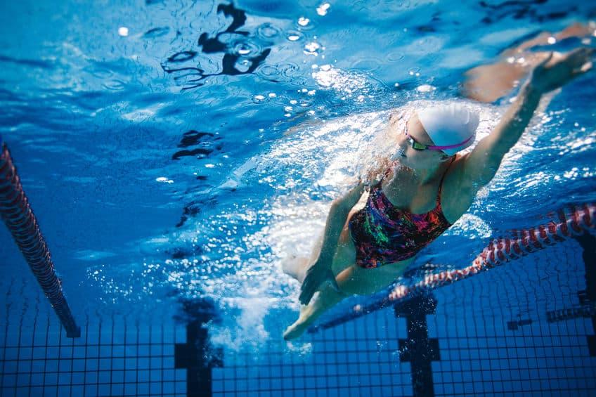A foto mostra uma mulher de maiô e touca de natação nadando em piscina olímpica com uma visão submersa na água.