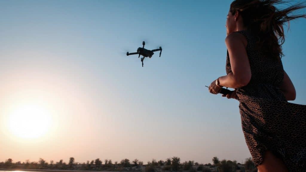 Imagem de uma mulher controlando um drone com câmera.