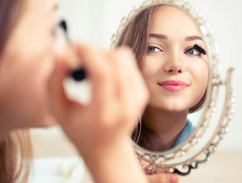Imagem de mulher passando rímel em frente a um espelho.