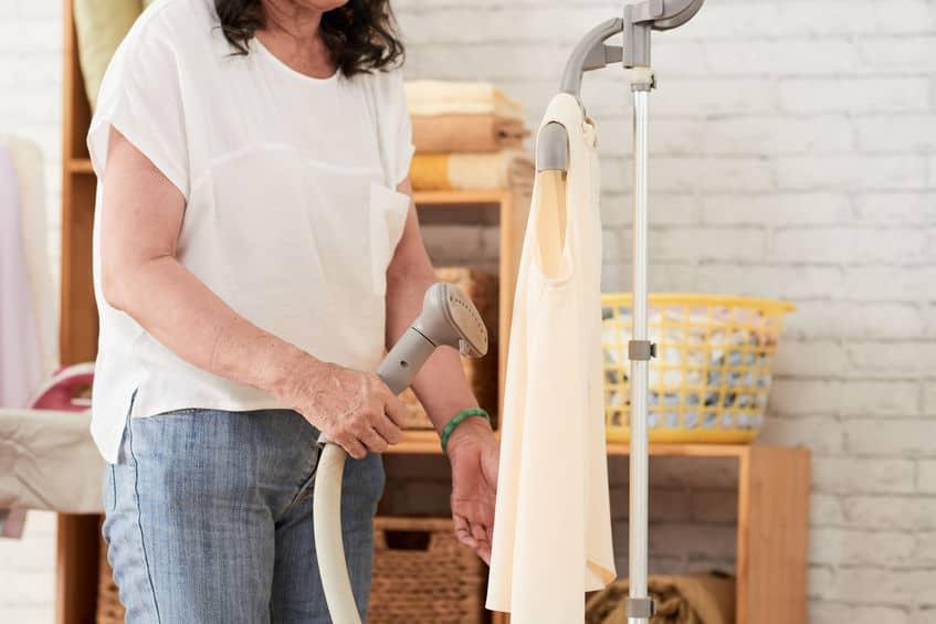 Imagem de uma mulher usando um vaporizador de roupas na lavanderia de casa.
