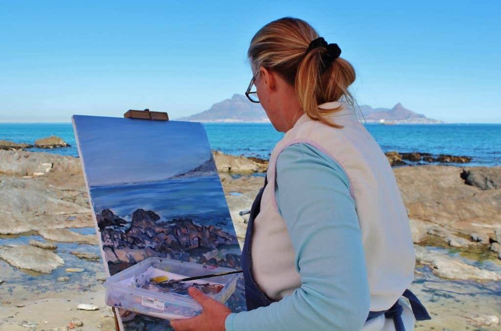 A foto mostra um quadro em destaque, apoiado em um cavalete de pintura, sendo pintado por uma mulher, tendo como cenário um mar.