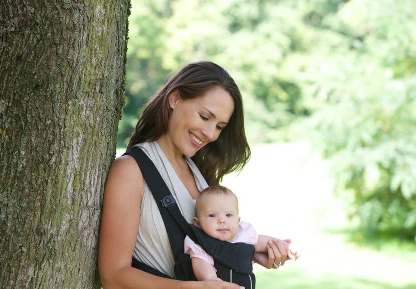 Imagem de mulher segurando bebê em parque com canguru.