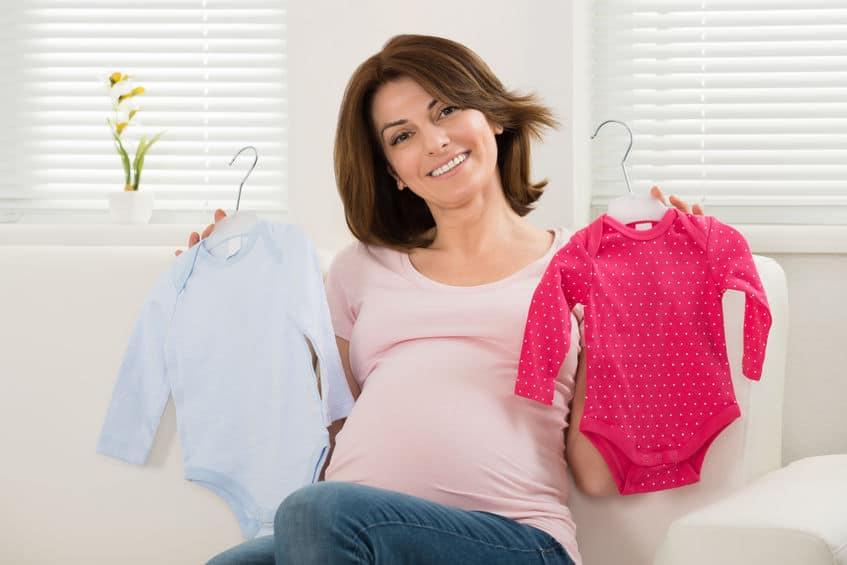 Mulher grávida segurando roupinhas de bebê no cabide infantil.