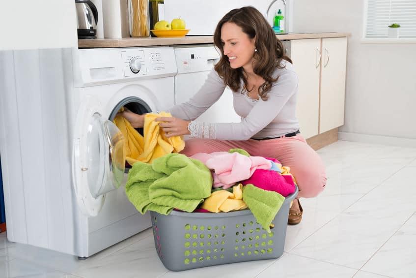 Imagem de mulher tirando roupas da máquina de lavar a colocando em cesto.