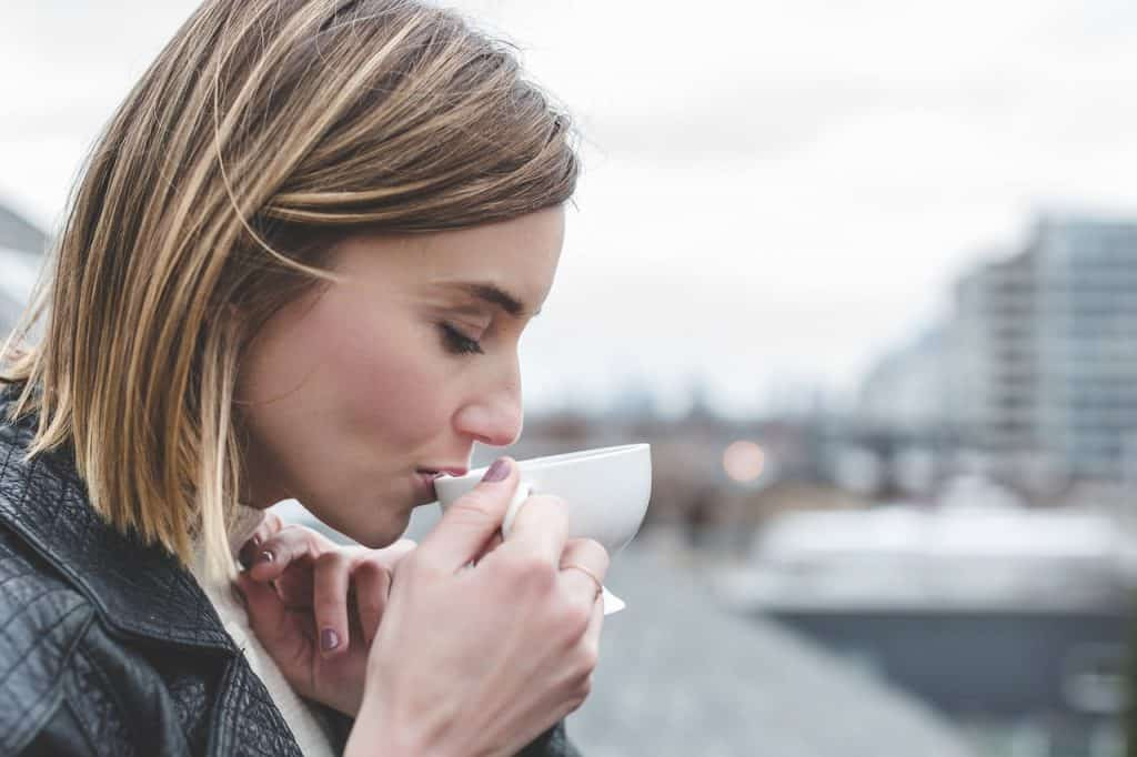 Imagem de mulher tomando chá preparado com infusor em um dia frio.