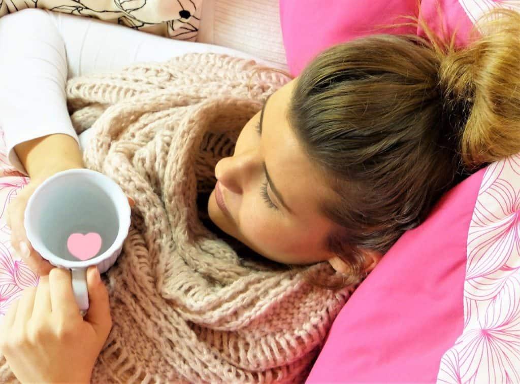 Mulher deitada tomando chá.