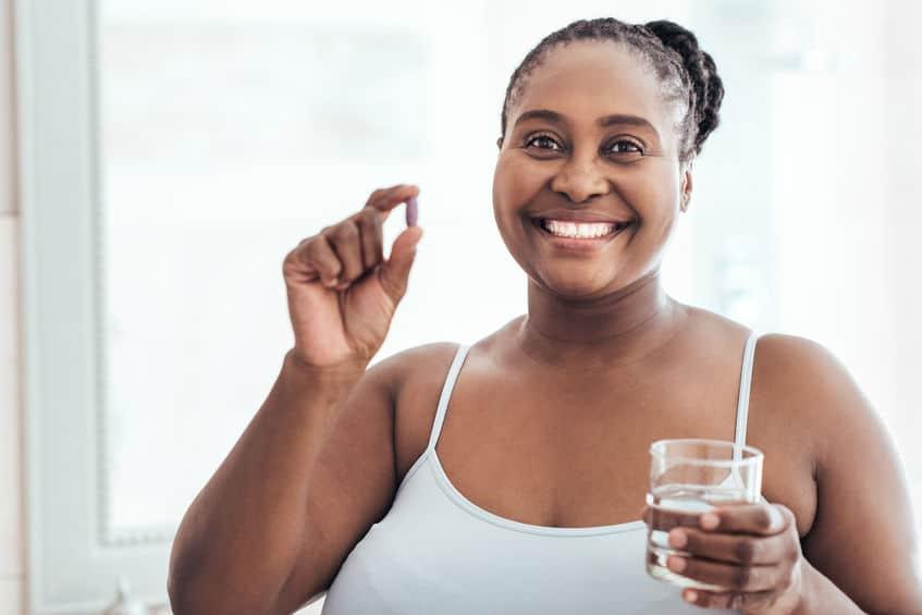 Mulher segurando comprimido e copo de água.