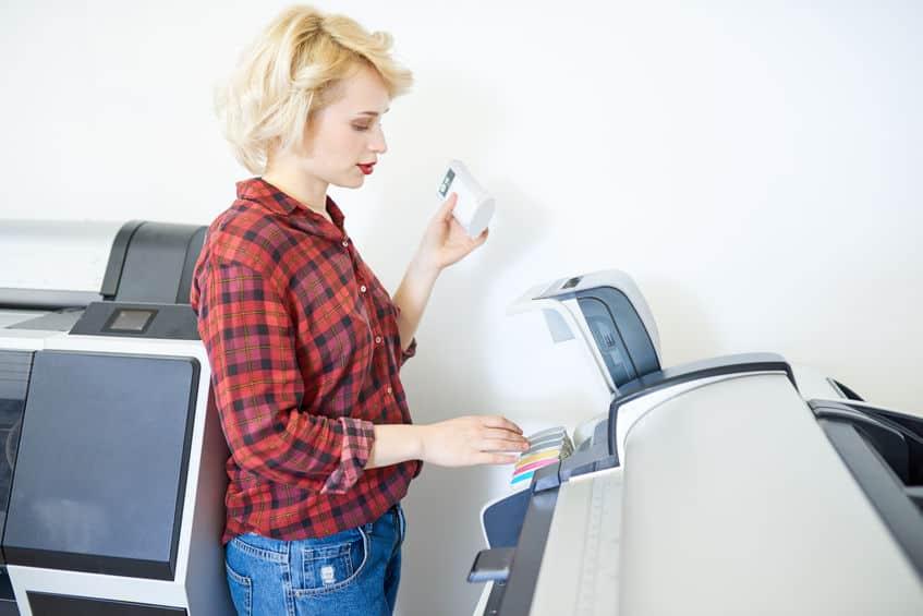 Mulher mexendo em impressora tanque de tinta.