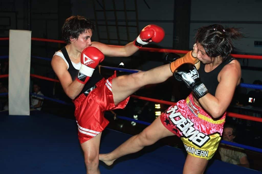 Imagem mostra duas pessoas lutando Muay Thai dentro de um ringue.