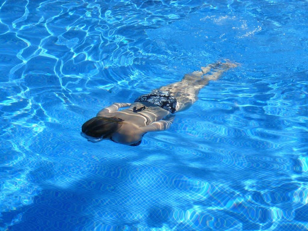 Imagem mostra uma mulher nadando em uma piscina.