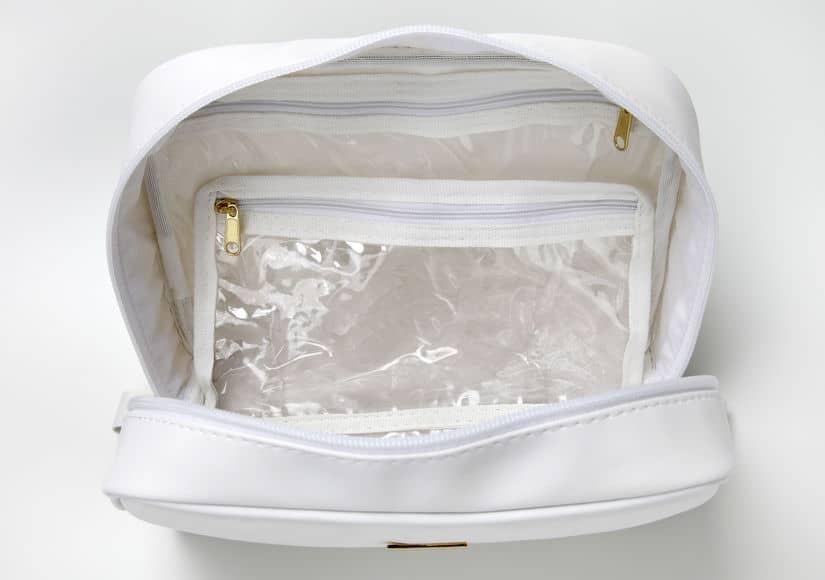 Foto de uma necessaire branca aberta, em um fundo também branco. Dentro da nécessaire, algumas divisórias de material plástico, transparente.