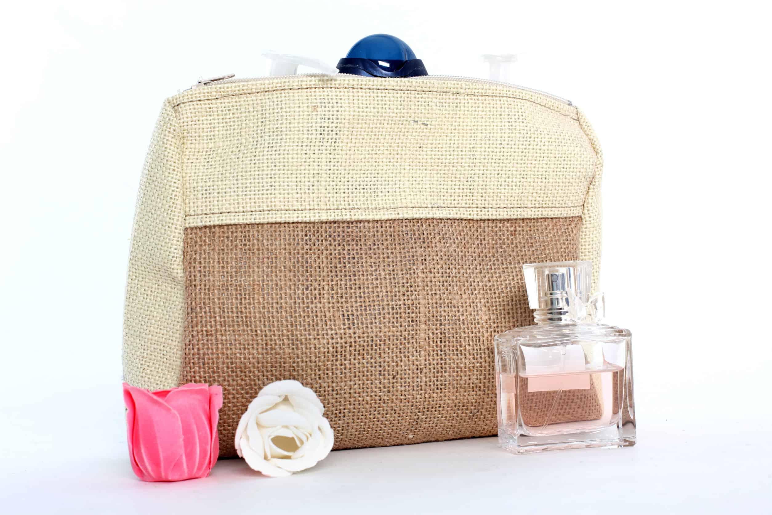 Foto de uma nécessaire feita de um material que imita palha, em dois tons, com um perfume e duas rosas na sua frente.
