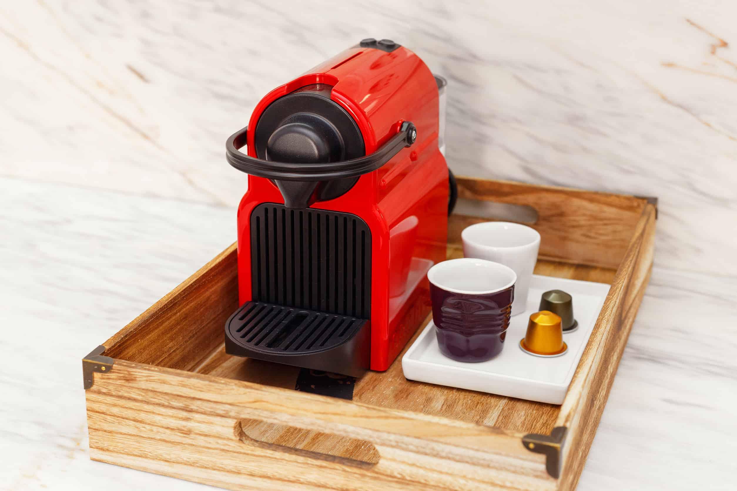Cafeteira Nespresso com cápsulas de café e copos ao lado.