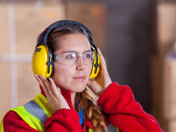Uma mulher com roupa de trabalho vermelha e amarela, usando óculos de proteção e protetores de ouvido.