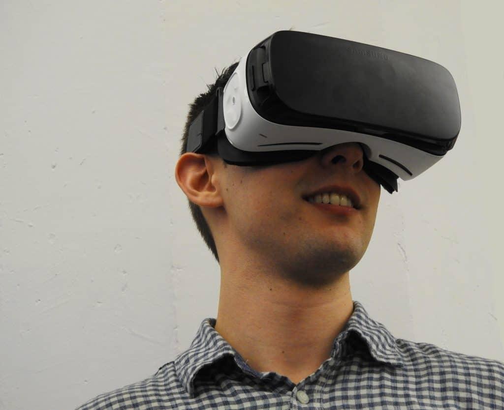 Imagem de um rapaz usando um Gear VR, óculos de realidade virtual.