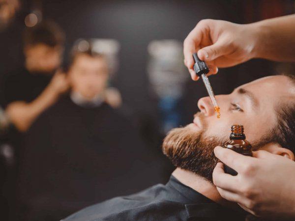 Imagem mostra um barbeiro aplicando óleo para barba em um cliente.