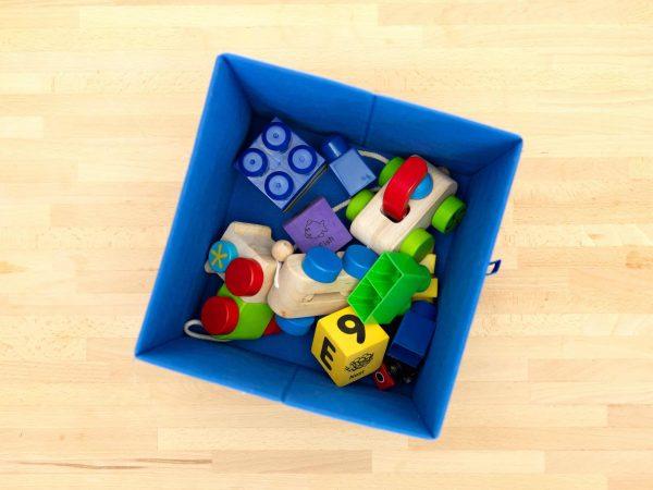 Caixa organizadora de brinquedos com carrinho e outros brinquedos.