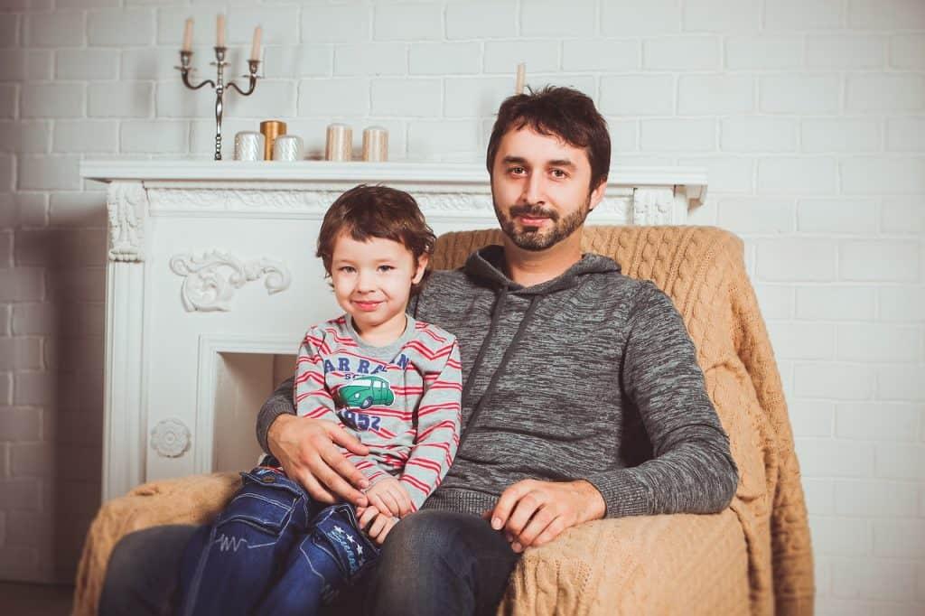 Imagem de pai e filho sentados em uma poltrona.