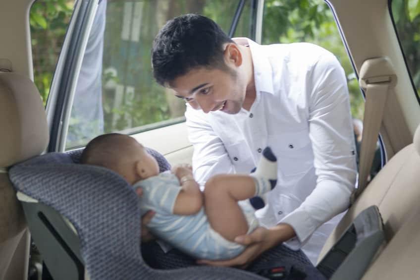 Pai colocando bebê em cadeirinha de bebê para carro.