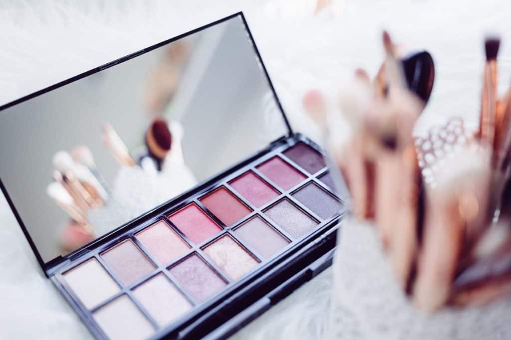 Foto de uma paleta de sombras retangular, com sombras em tons de rosa, cinza e roxo, ao lado de um porta pinceis, com vários pincéis de maquiagem.