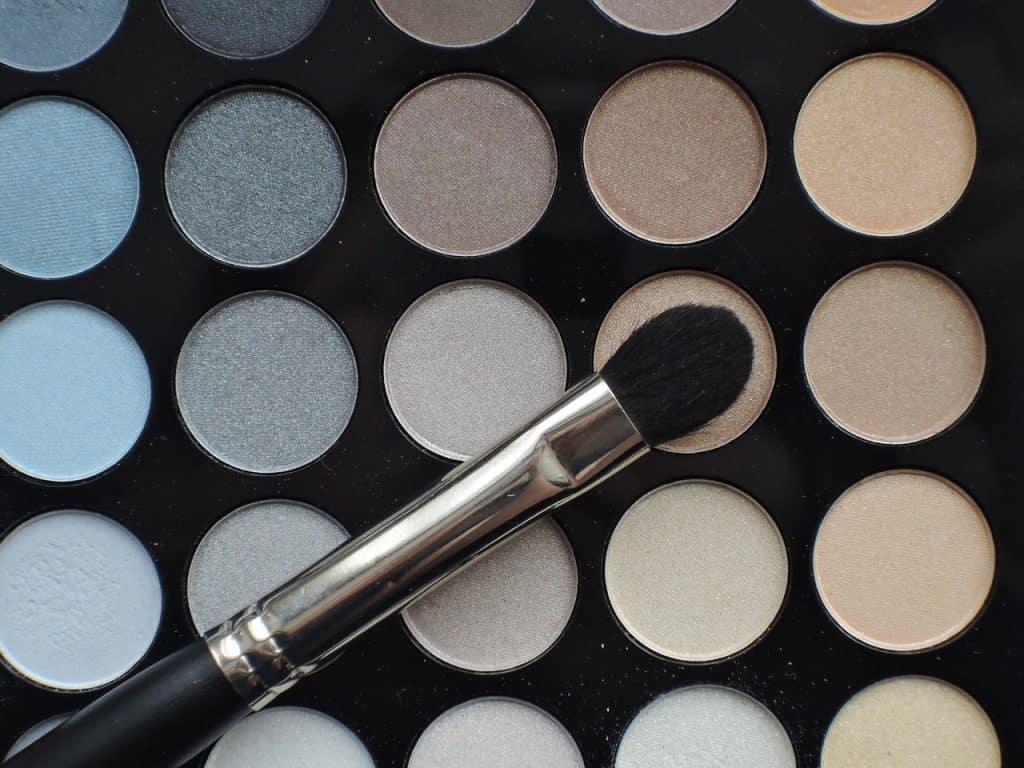 Imagem de pincel de maquiagem sobre paleta de sombras.