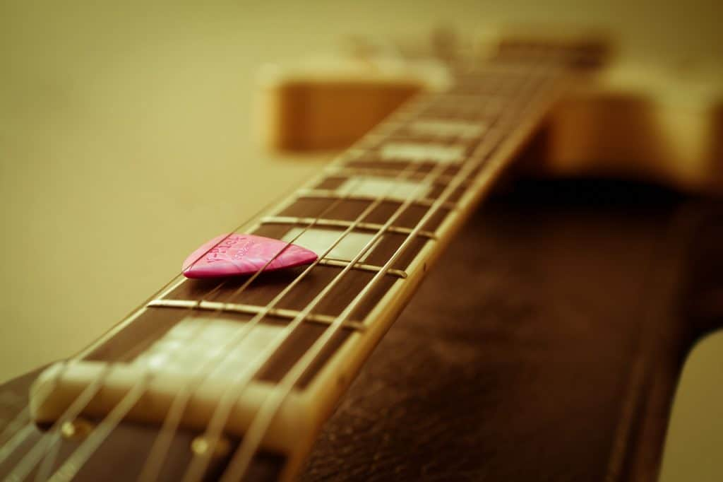 A blue guitar pick stuck between the strings and the neck of a guitar.