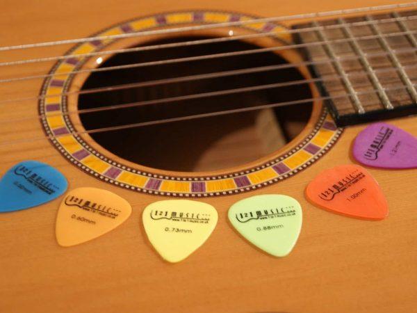 Seis palhetas em cima do corpo de um violão, logo abaixo das cordas.