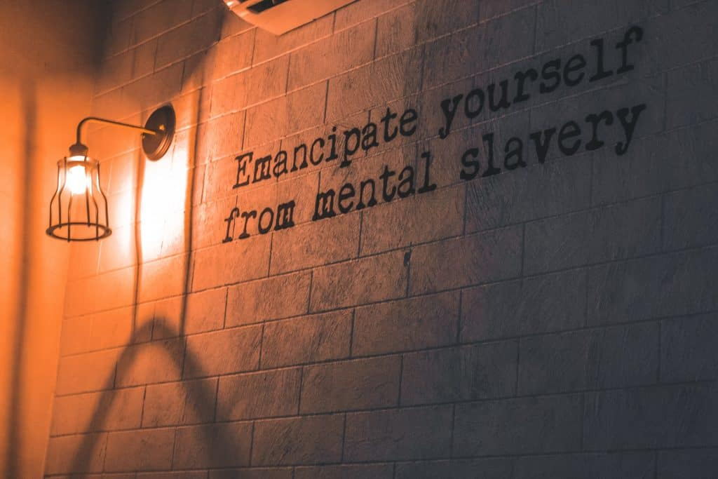 """Arandela acesa em parede com o escrito: """"Emancipate yourself from mental slavery."""""""