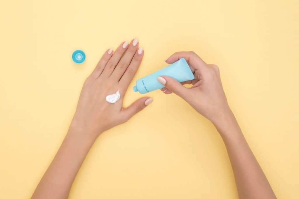 Imagem de mulher demonstrando o uso de um creme para assaduras sobre a pele da mão direita.