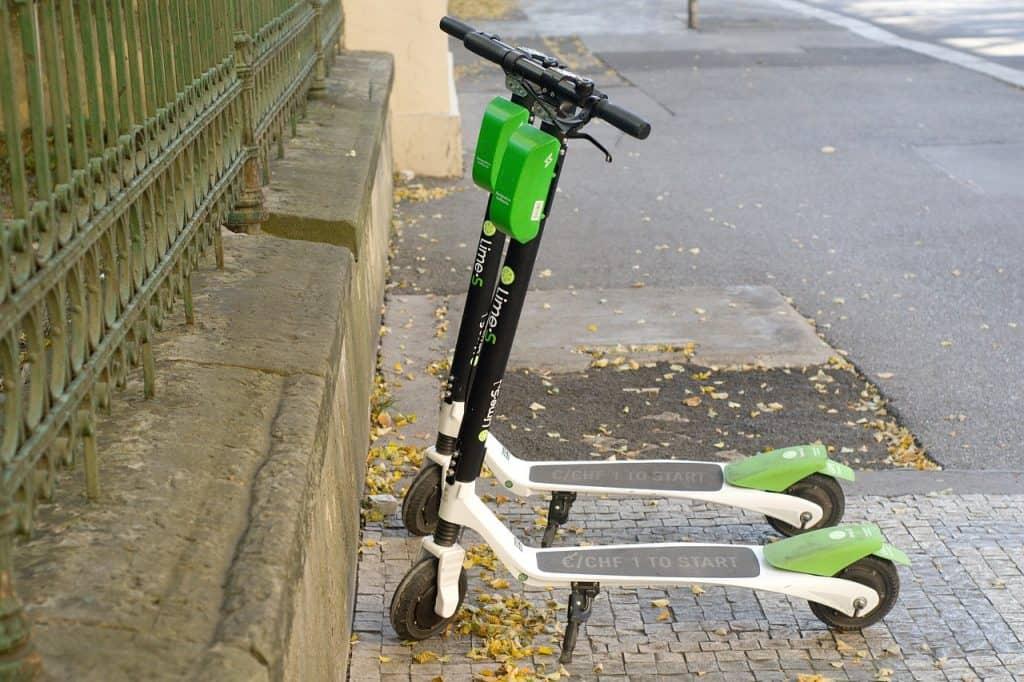 Imagem mostra dois patinetes elétricos 'estacionados' em uma calçada com destaque para suas baterias ecológicas.