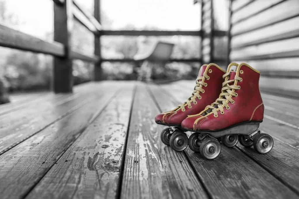 Imagem de patins vermelho sobre superfície de madeira.