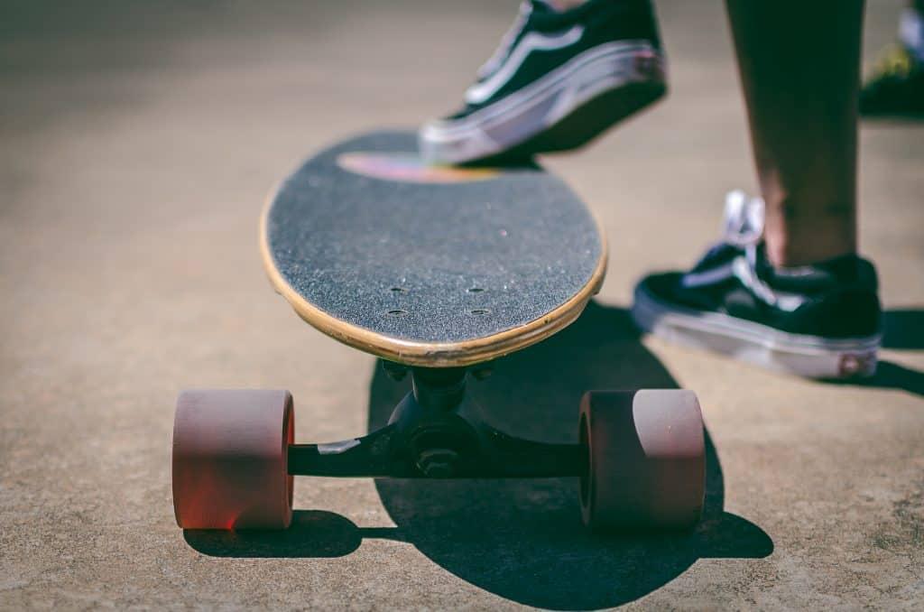 """Imagem mostra um close do """"bico"""" de um longboard, com foco nas suas duas rodas frontais."""