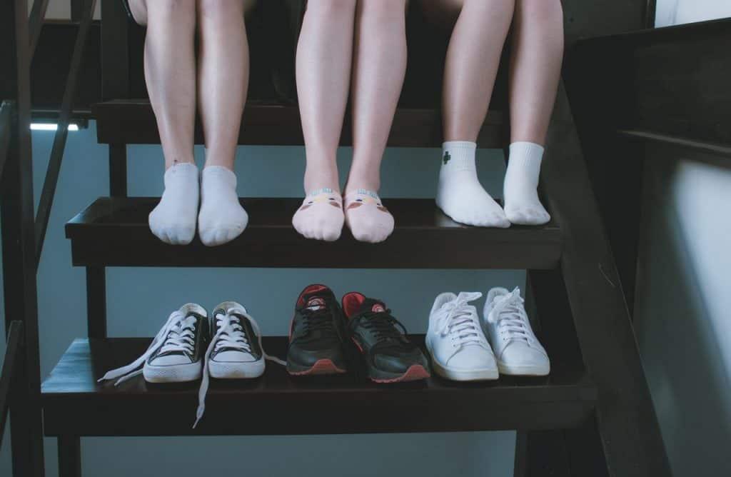 Foto que mostra do joelho pra baixo de três pessoas que estão sentadas em uma escada vestindo meias. No degrau de baixo, os tênis de cada um.