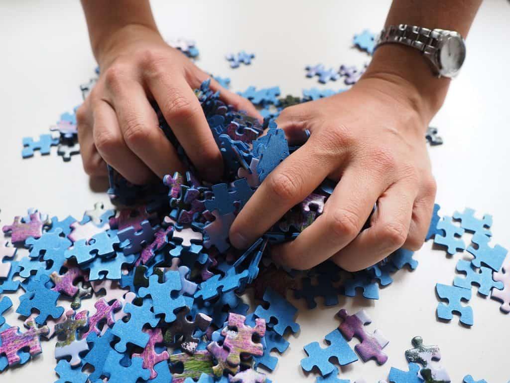 Mãos segurando um punhado de peças de um quebra-cabeça colorido.
