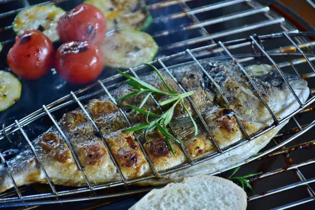 Na foto está um peixe assando na churrasqueira.