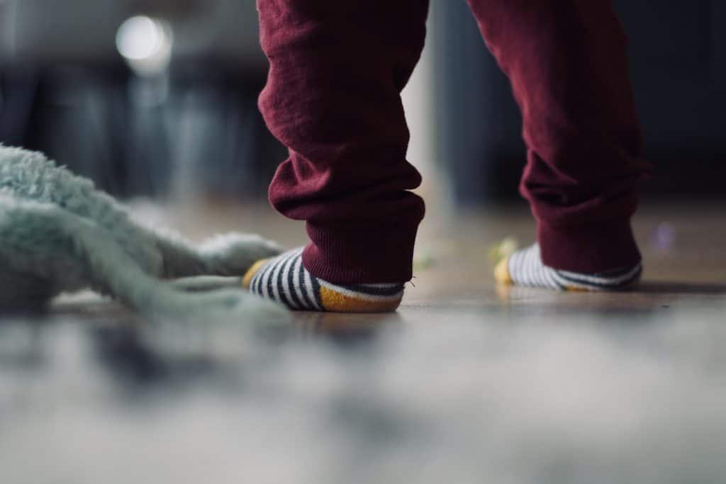Na foto os pés de um bebê em pé usando meias listradas e calça cor vinho.