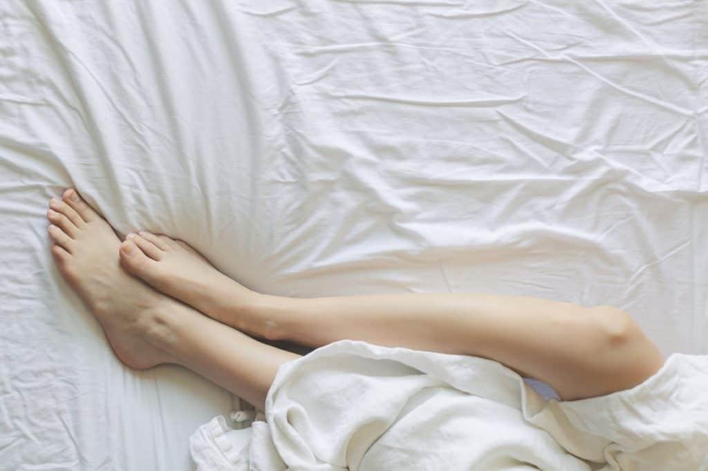Foto das pernas depiladas de uma pessoa deitada em uma cama com lençol branco. Em cima das pernas, um outro lençol da mesma cor. Nenhuma outra parte do corpo está aparente.