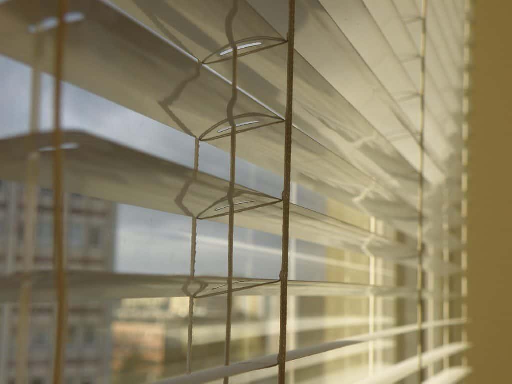 Imagem em close de uma persiana horizontal branca.