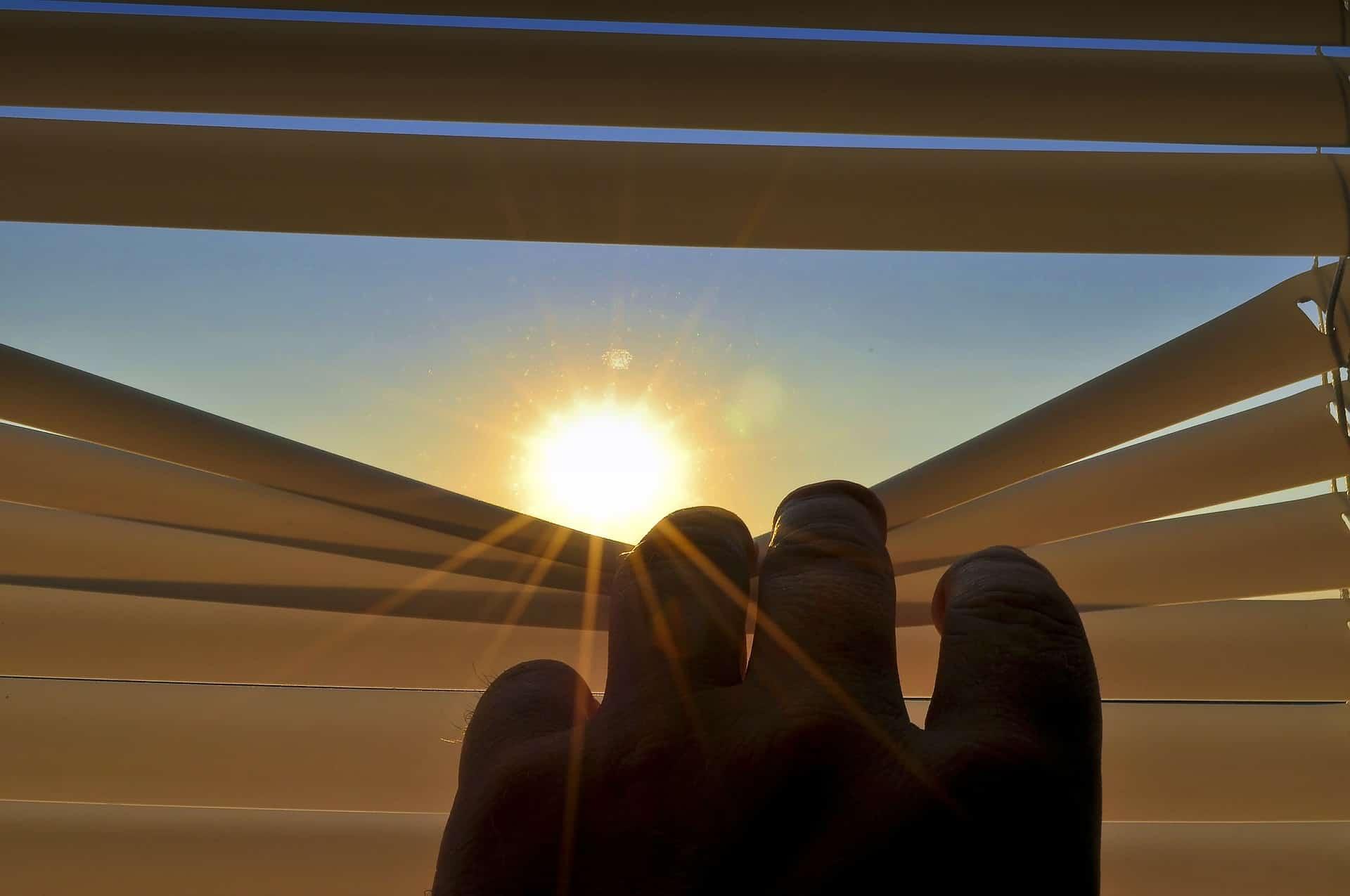 Imagem mão abrindo parcialmente um persiana para observar o sol.