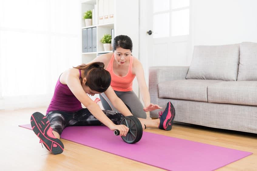Imagem de mulher utilizando roda de exercícios abdominais com o auxílio de uma professora.