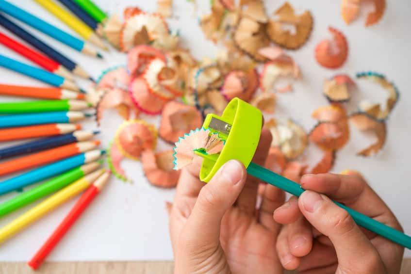 Mão apontando lápis, ao fundo tem sujeira de lápis apontado com lápis de cor ao redor.
