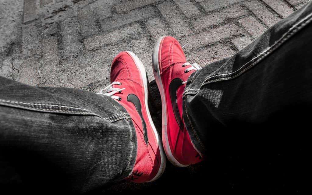 Imagem de pessoa vestindo calça jeans escura e Nikes vermelhos em modelo para skate.