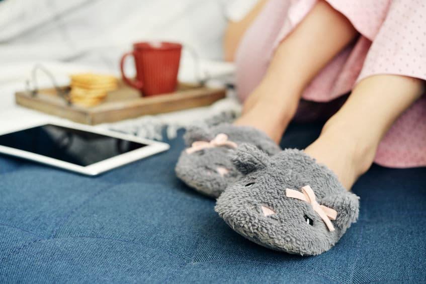 Imagem das pernas de uma mulher com pantufa na cama com bandeja de café e tablet ao lado.