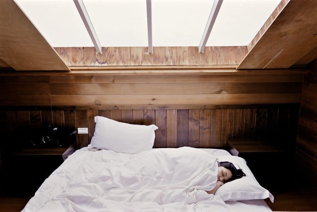Imagem mostra moça deitada na cama com travesseiros e roupa de cama brancos.